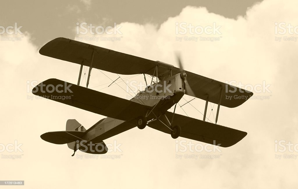 Black and white photo of Tiger Moth flying through clouds royalty-free stock photo