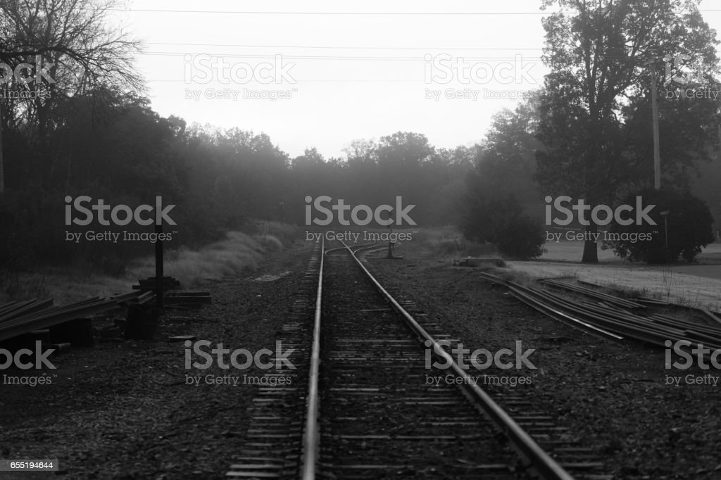 Black and white photo of train tracks on a foggy morning. stock photo