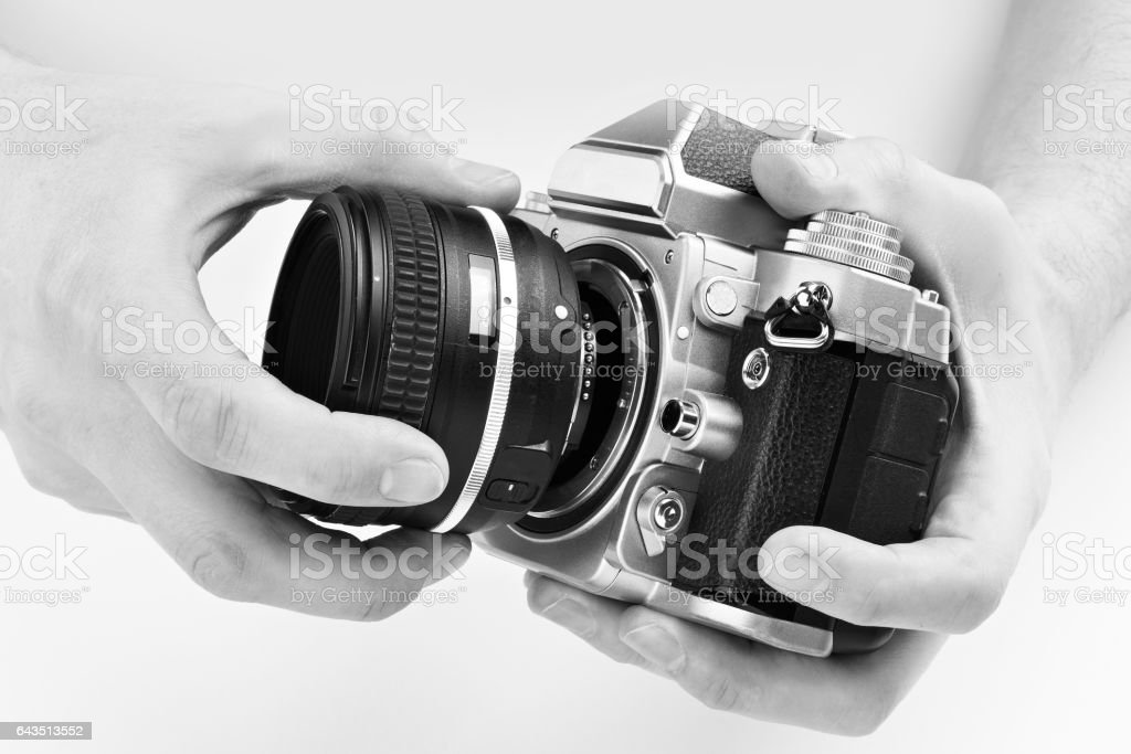 Black and white photo SLR camera in hands of photographer stock photo