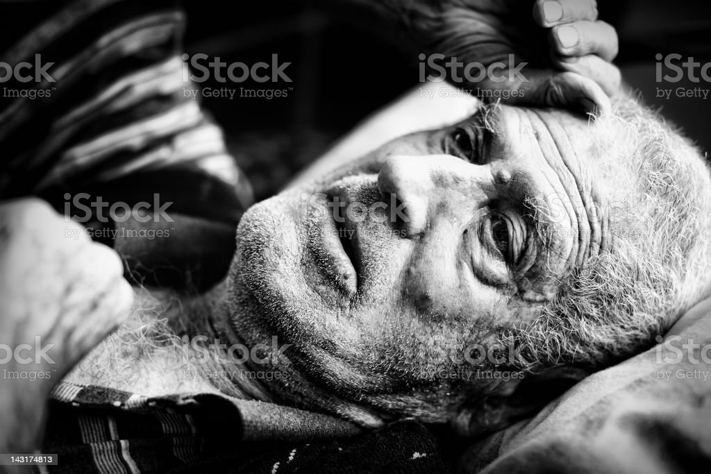 Black and white photograph or an elderly man laying down  stock photo