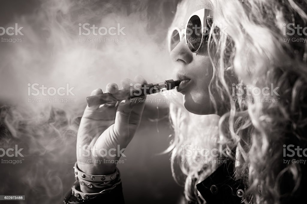 Black and white picture of woman smoking e-cigarette stock photo