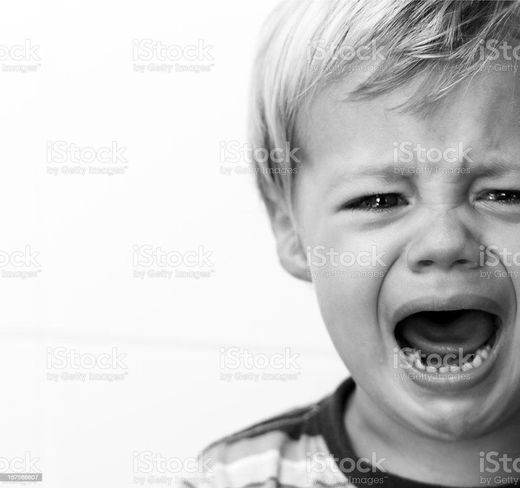 Black and white portrait of a crying young boy stock photo
