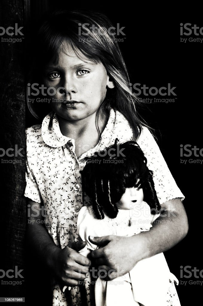 Black and white portrait of a girl holding a doll royalty-free stock photo