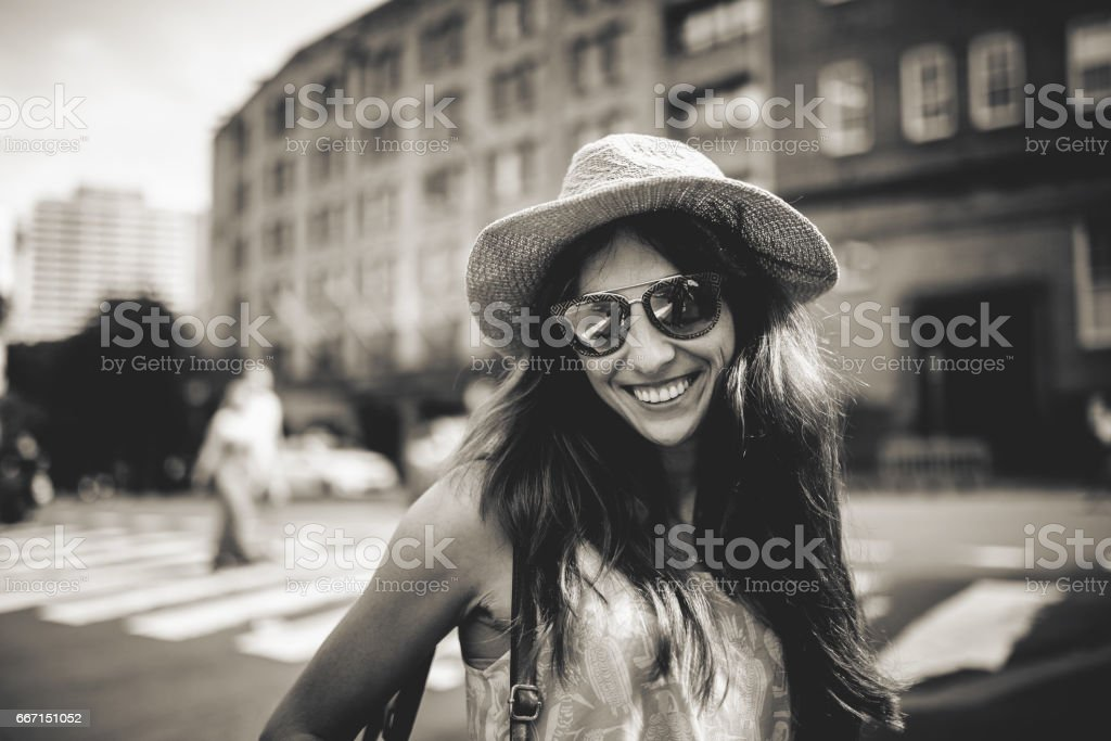 Black and white portrait of cute smiling girl in sunglasses with city buildings in the background. stock photo