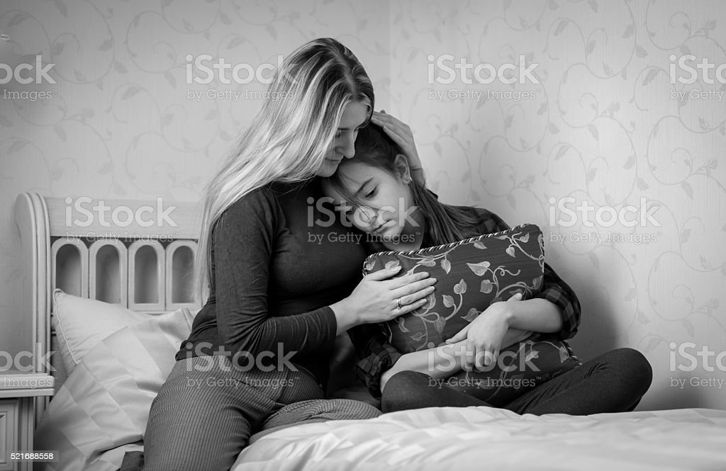 Black and white portrait of mother consoling teenage daughter on stock photo