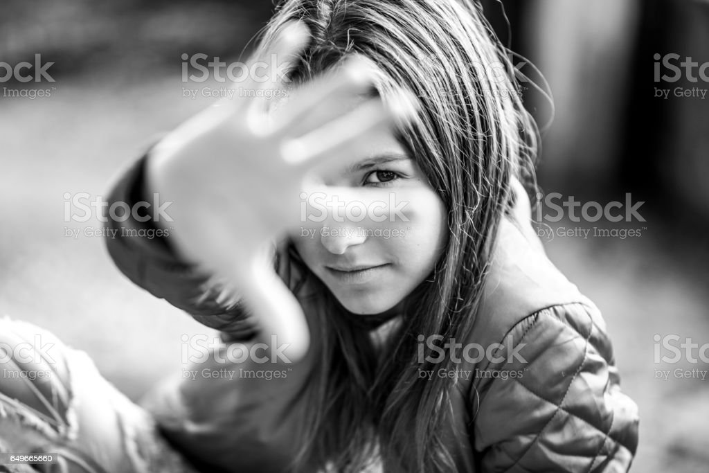Black and white portrait of teenage girl hiding behind her hand stock photo