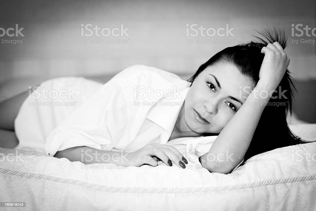 Black and white portrait of woman in bedroom stock photo