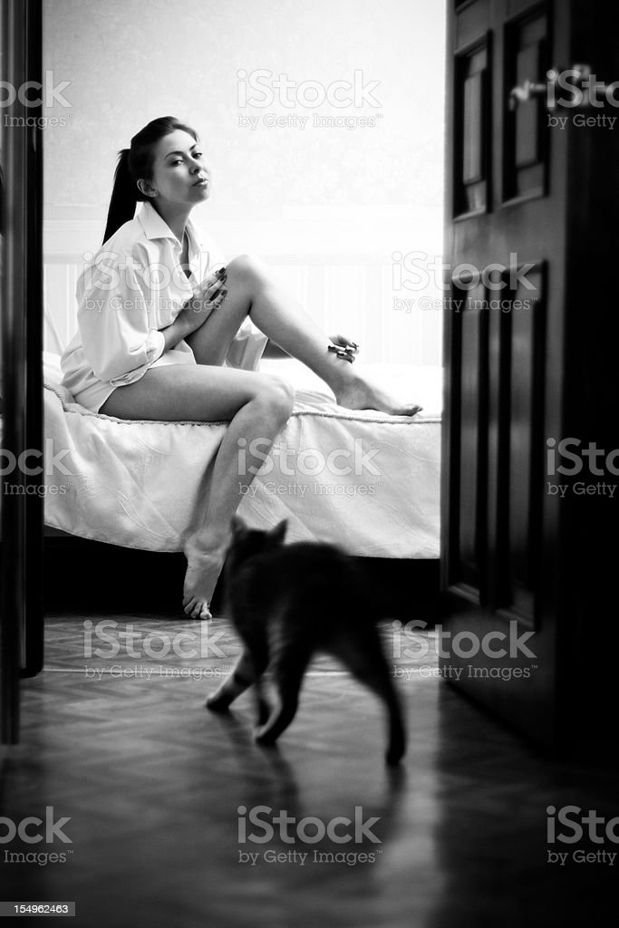 Black and white portrait of woman in bedroom with cat stock photo