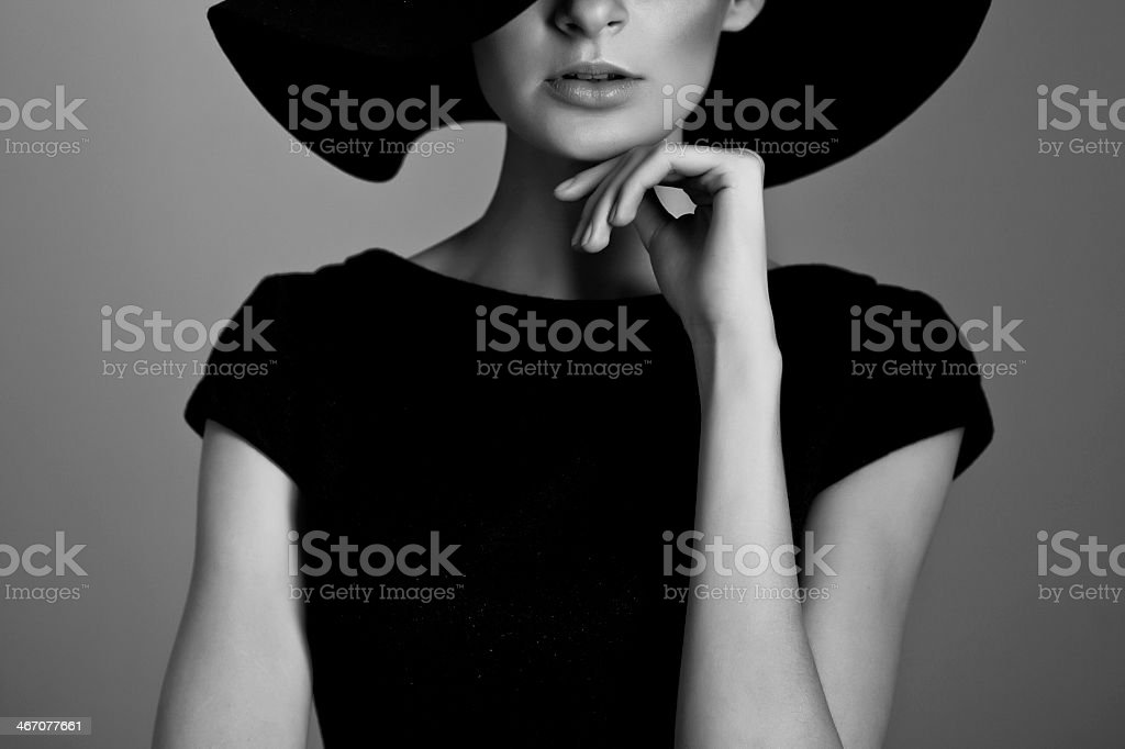 Black and white portrait of woman in black shirt and hat stock photo