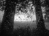 Black and white raindrops on the glass, dramatic storm clouds
