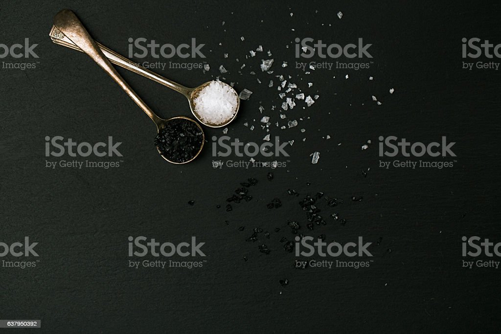 black and white salt in spoons stock photo