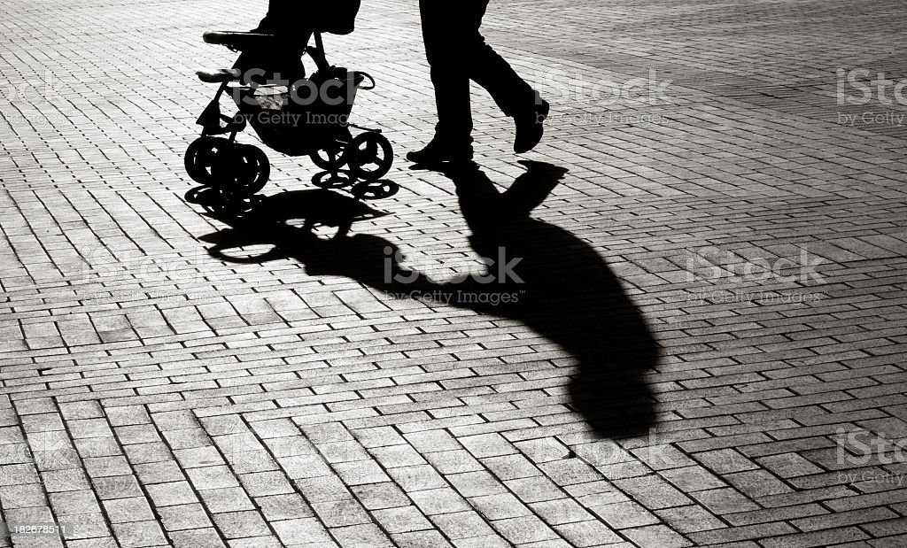Black And White Shadow Of Baby Carriage On Sidewalk Stones stock photo