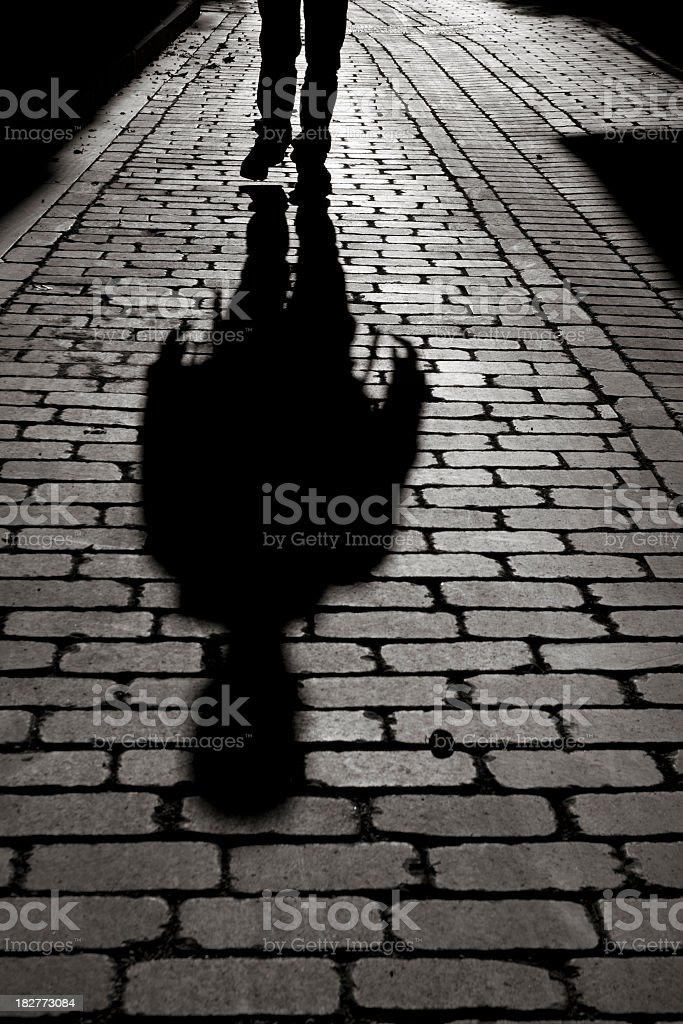 Black And White Shadow Of Man Walking On Sidewalk stock photo