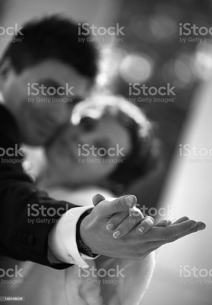 Black and white shot of a couple holding hands while dancing royalty-free stock photo