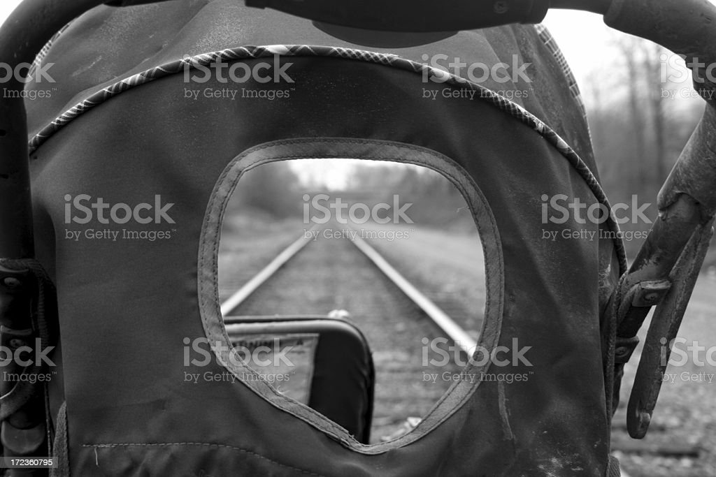 Black and white shot of baby carriage on train tracks stock photo