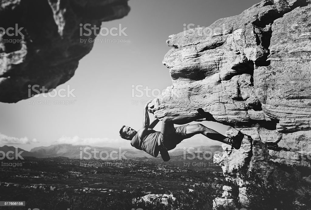 Black and white shot of free climber hanging on rock stock photo