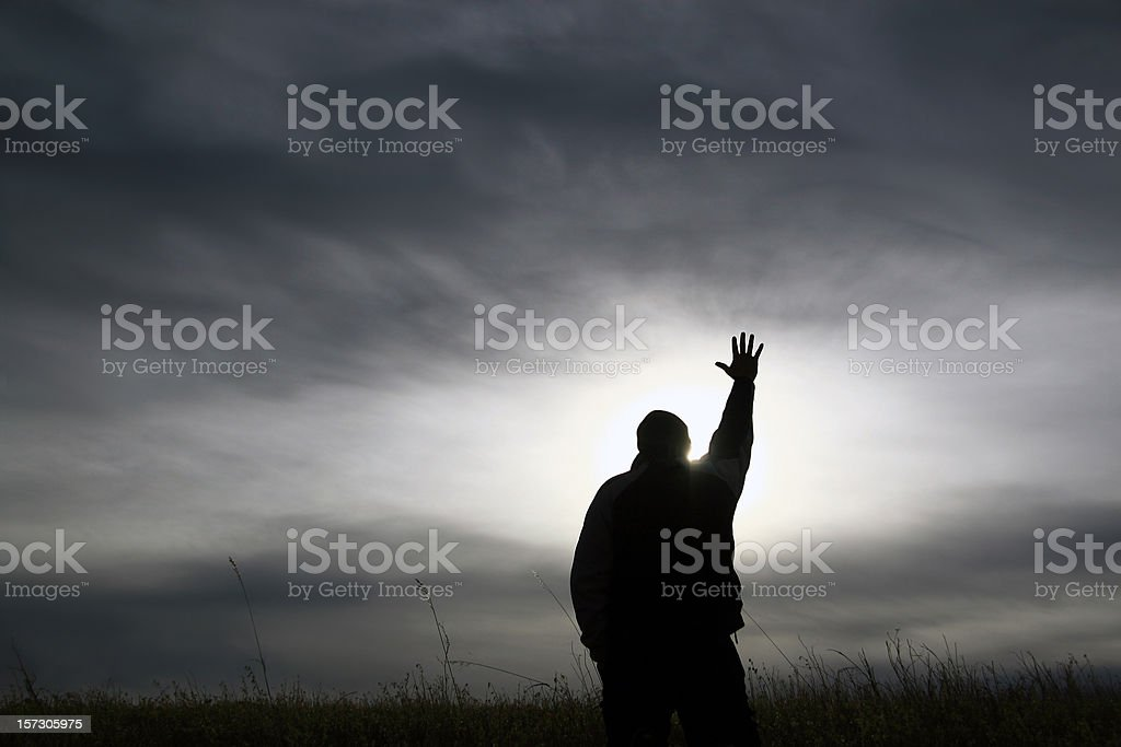 Black and White Silhouette Man With Hand Outstretched in Worship stock photo