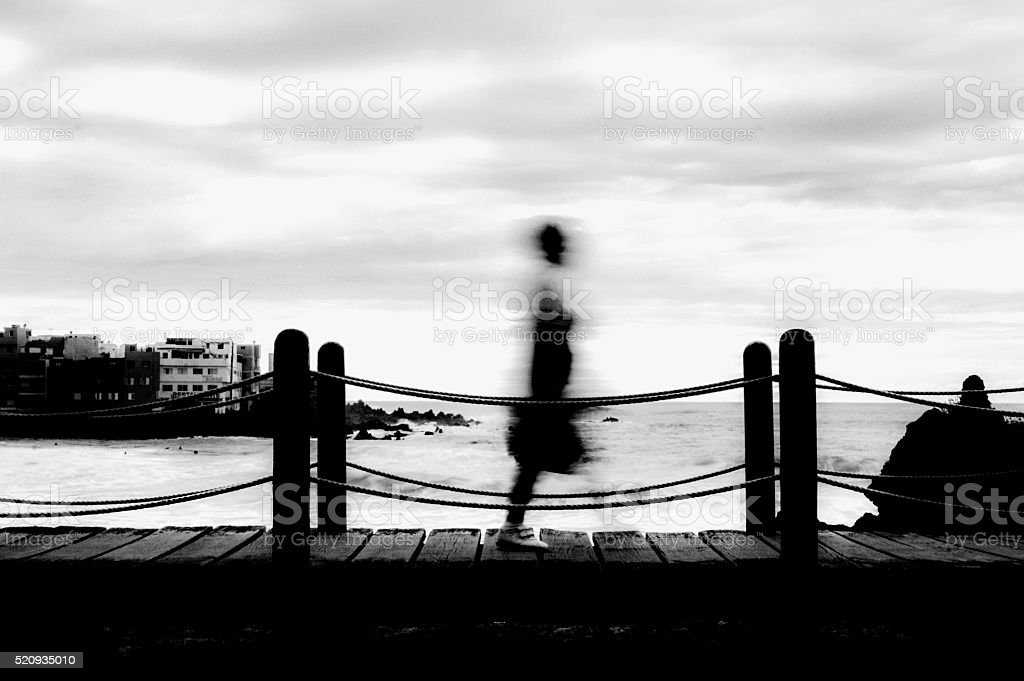 Black and white silhouette of older woman crossing a bridge stock photo