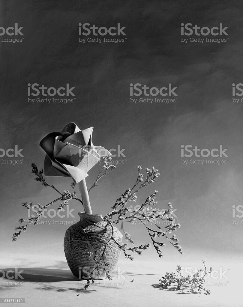Black and white still life with paper rose on wallpaper. stock photo
