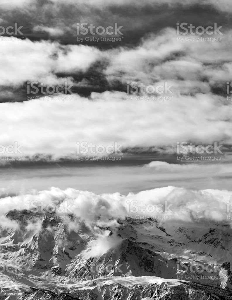 Black and white sunlight snowy mountains in clouds stock photo