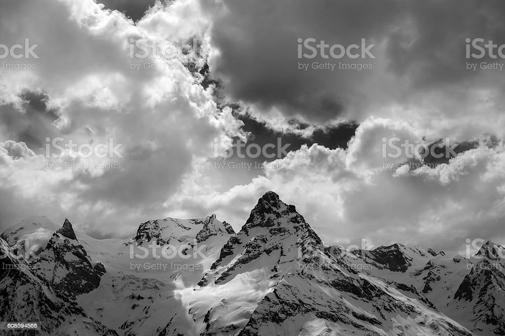 Black and white view on evening mountains in sunlight clouds stock photo