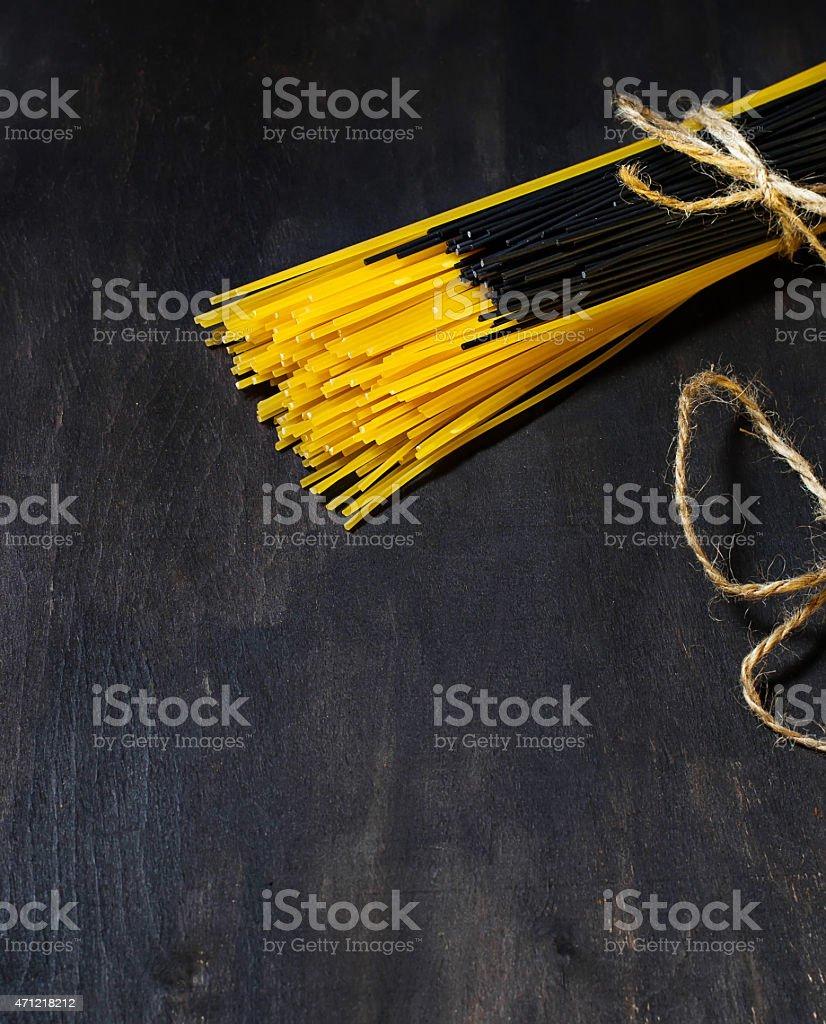 Black and yellow spaghetti on dark background stock photo