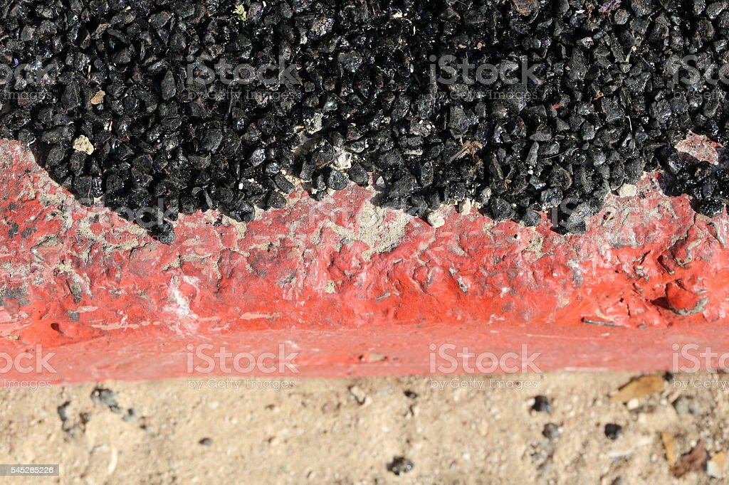 Black Asphalt Layer on a Red Curbstone stock photo