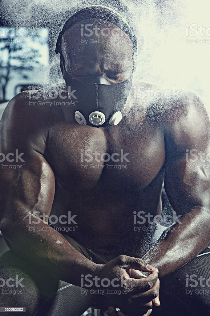 black athlete wearing mask  working out in a gym stock photo