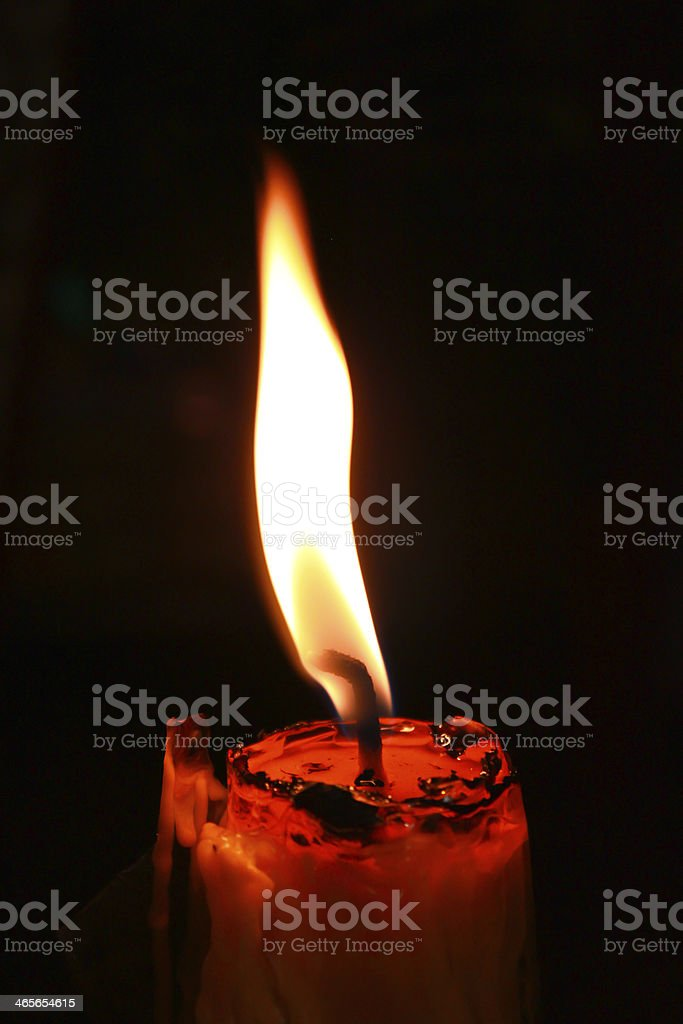 A black background and a burning candle stock photo