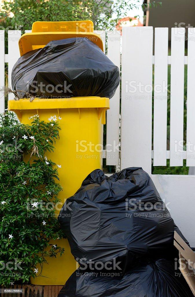 Black bag plastic in yellow trashcan bin stock photo