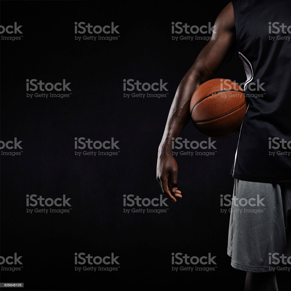 Black basketball player standing with a basket ball stock photo