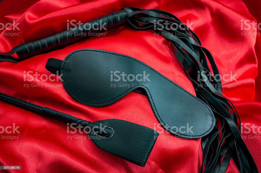 Black BDSM sex toys on red silk stock photo