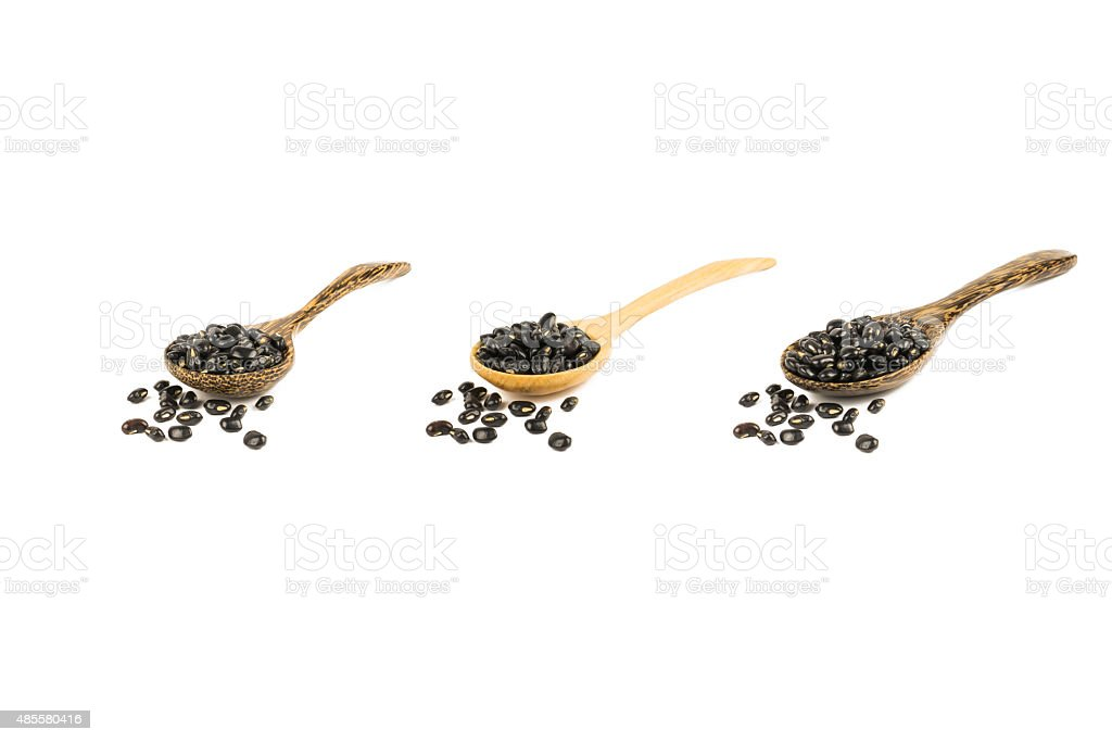 Black bean in wood spoon isolated on white stock photo
