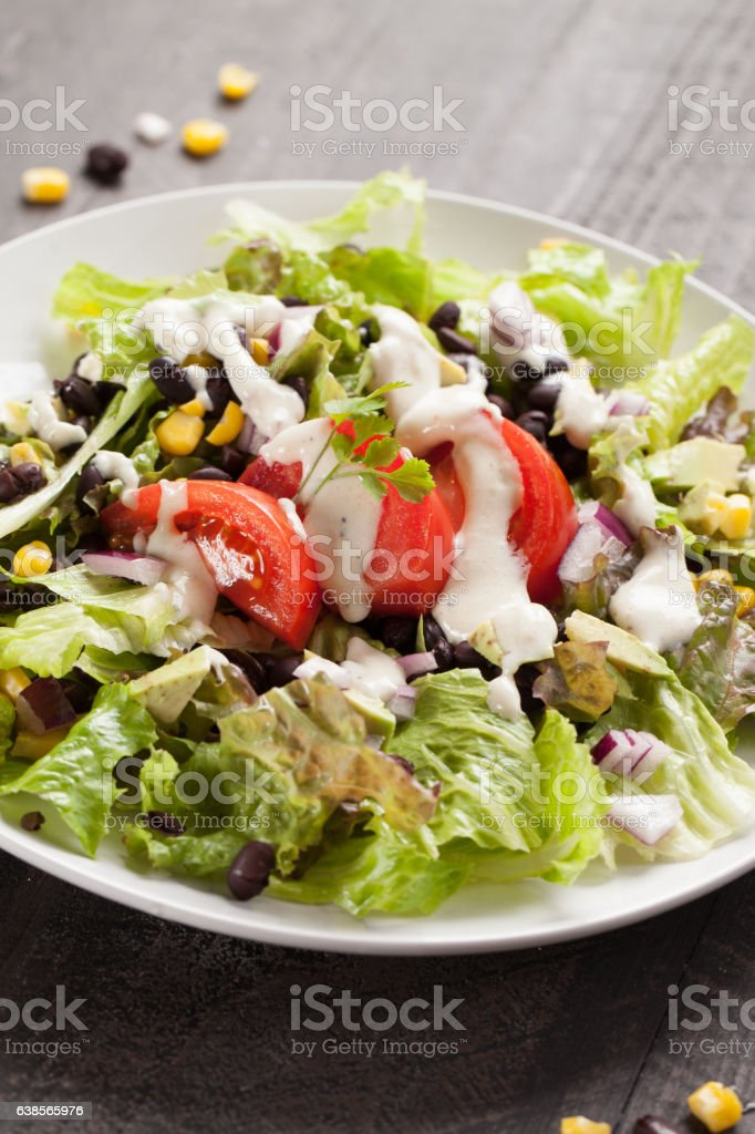 Black Bean Southwest Salad with white dressing stock photo
