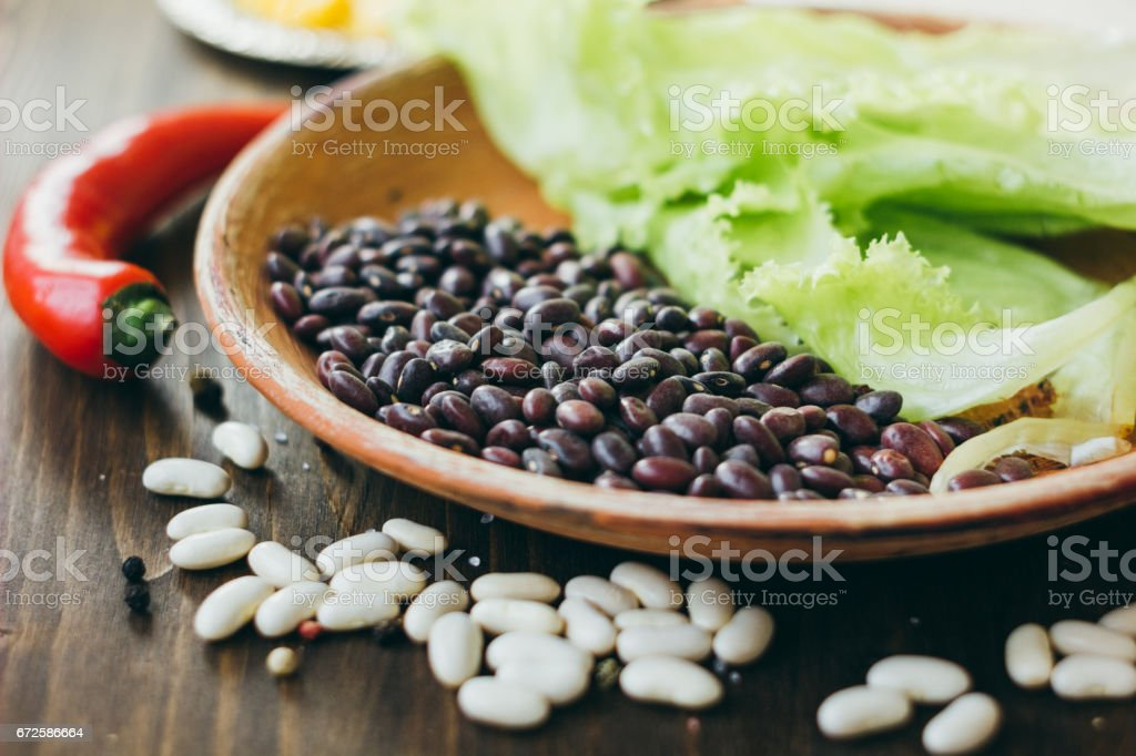 Black beans on brown pottery plate over wooden board. stock photo