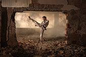 Black belt martial artist practicing high kick among ruins.