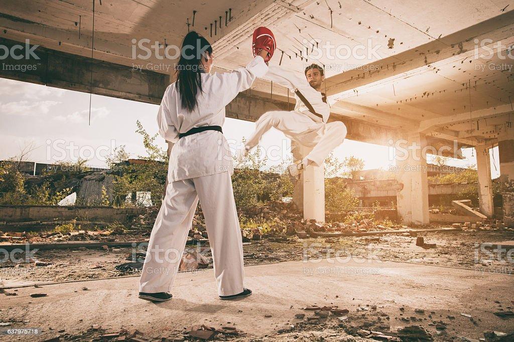 Black belt martial artist practicing jump kick with sparring partner. stock photo