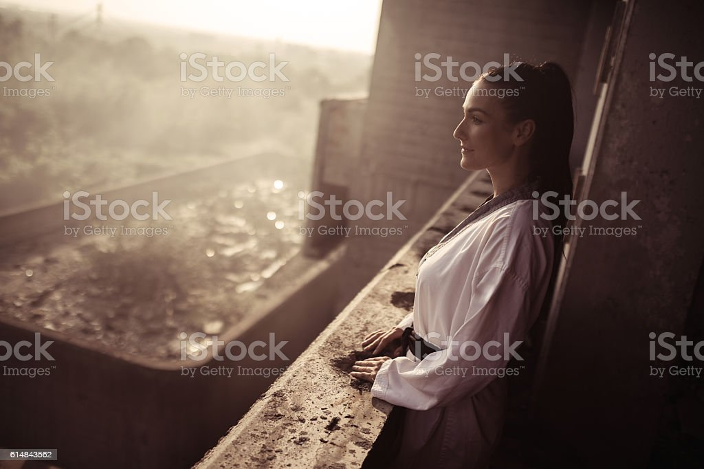 Black belt martial artist standing on a balcony and smiling. stock photo