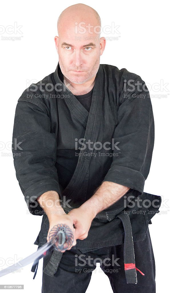 Black belt ninju warrior with sword at the ready. stock photo