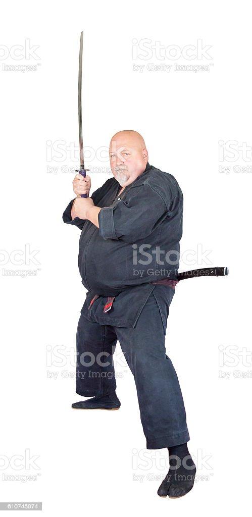 Black belt ninju warrior with sword at the ready. stock photo