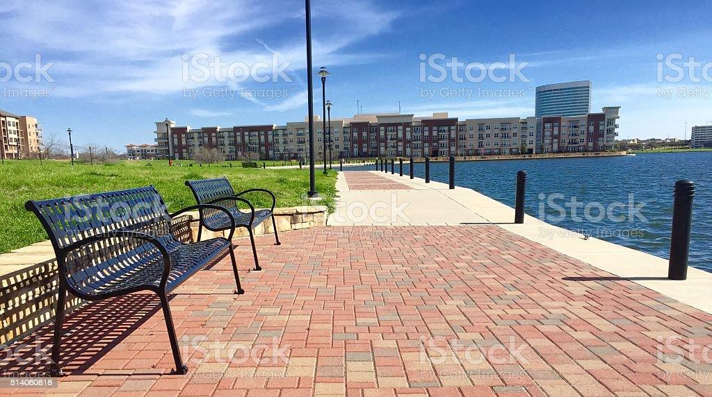 Black benches along lakeside urban center stock photo