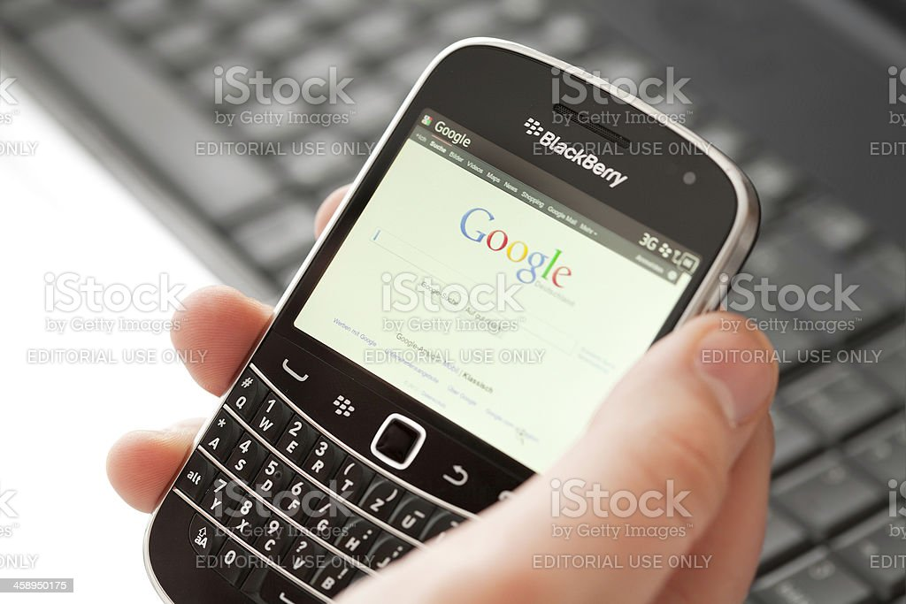 Black Berry smartphone in male hand stock photo