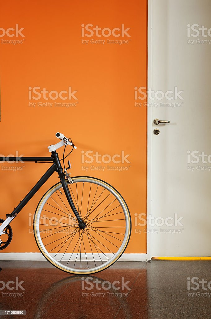 Black bicycle against an orange wall royalty-free stock photo