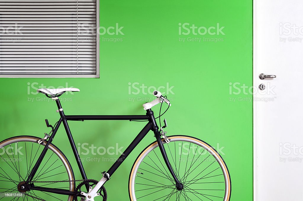 Black bicycle green wall royalty-free stock photo