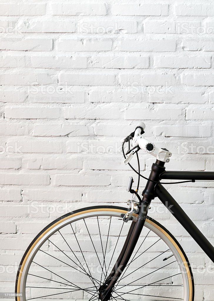 Black bicycle over a brick wall royalty-free stock photo