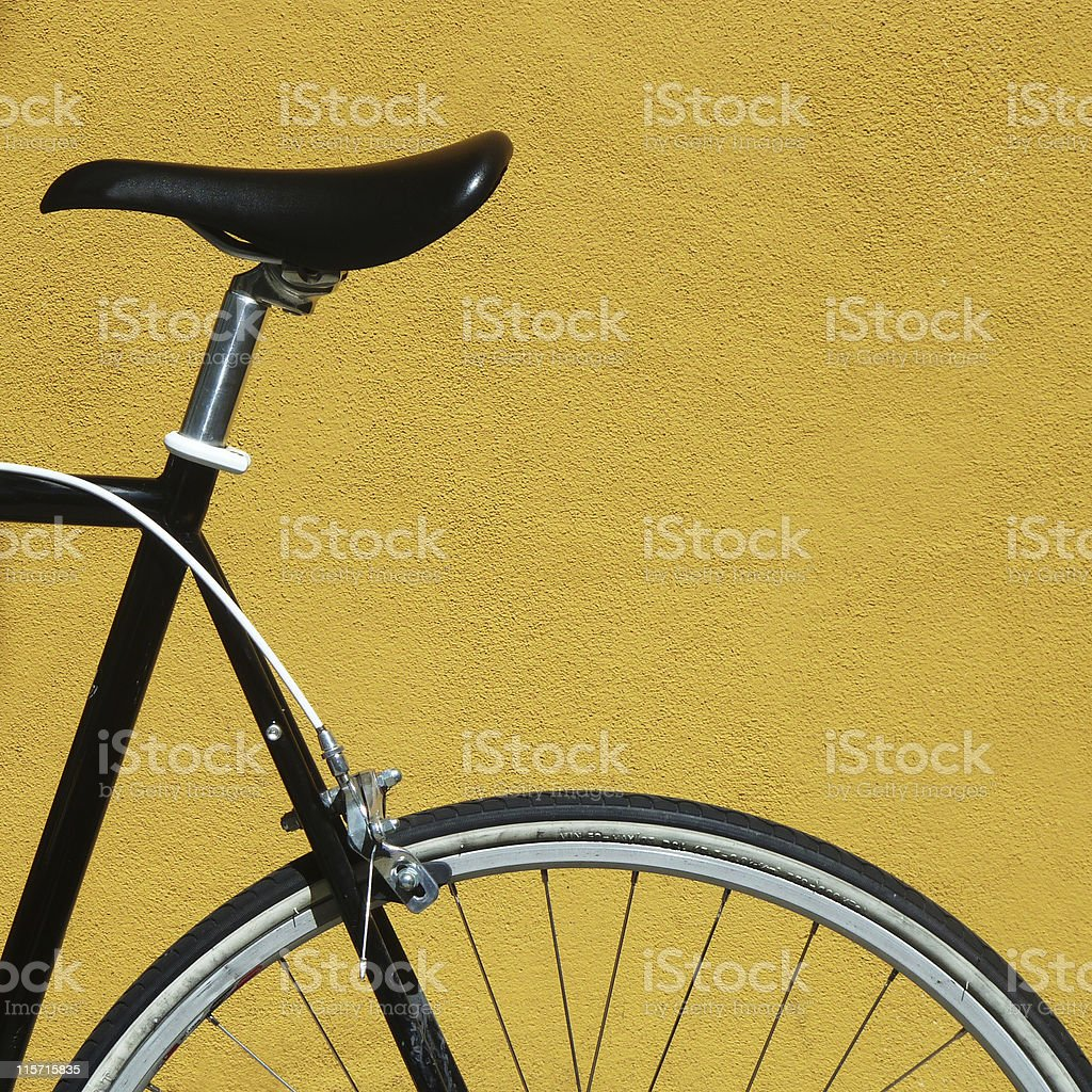 Black bike against a yellow wall royalty-free stock photo
