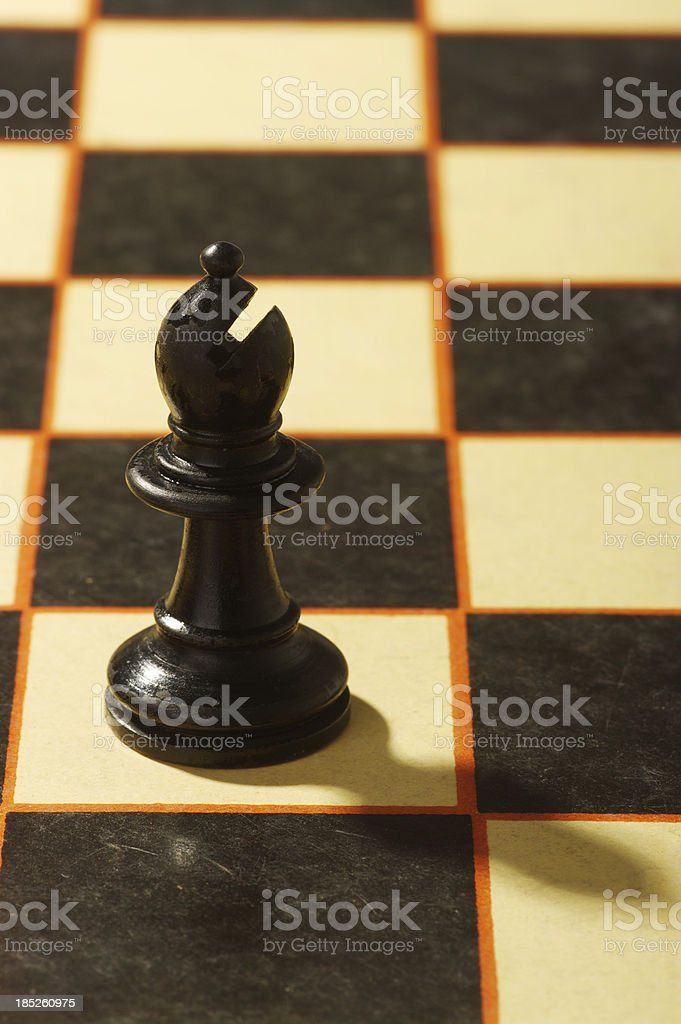 Black Bishop Chess Piece On Old Board stock photo