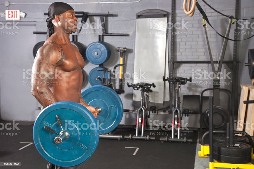 Black body builder curling heavy barbell in muscle gym stock photo