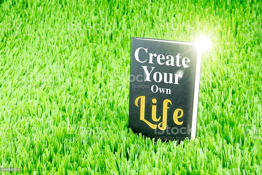 Black book on grass with Create your own life stock photo