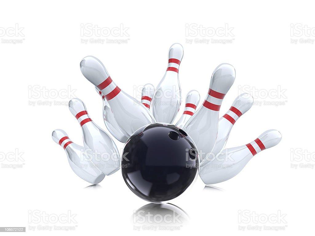 A black bowling ball knocking down ten bowling pins stock photo